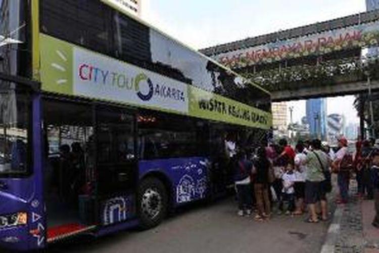 Warga mengantre berebutan naik bus tingkat wisata di Halte Bundaran Hotel Indonesia, Jakarta Pusat, Minggu (2/3/2014). Sebanyak 5 bus tingkat yang dioperasikan belum mampu sepenuhnya melayani warga DKI Jakarta. Pasalnya warga harus rela yang antre berjam-jam untuk bisa naik bis tersebut.