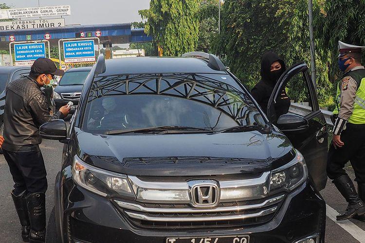 Petugas gabungan Polri dan Dishub meminta penumpang untuk berpindah bangku dalam rangka physical distancing dan penerapan PSBB di pintu tol Bekasi Timur, Bekasi, Jawa Barat, Rabu (15/4/2020). Pemberlakuan PSBB di Jawa Barat yang berlaku hari ini masih ada pengendara yang masih belum tertib dalam menjalankan arahan pengendalian COVID-19.