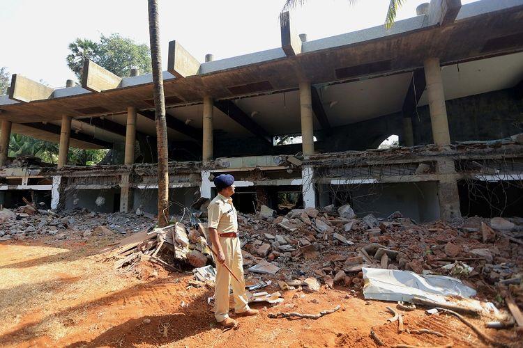 Petugas polisi India berdiri di dekat sisa bangunan mewah milik miliarder Nirav Modi yang diledakkan menggunakan dinamit oleh pemerintah karena diduga dibangun menggunakan uang hasil penipuan, Jumat (8/3/2019).