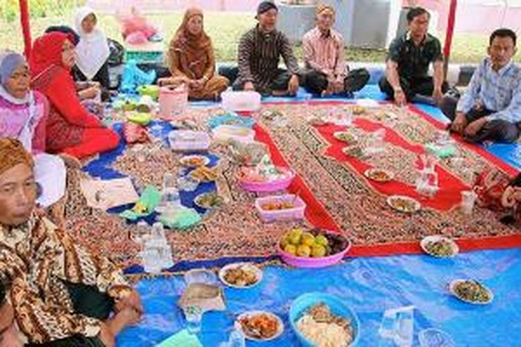 Warga etnis Jawa yang tinggal di Kota Sawahlunto, Sumatera Barat, memotong tumpeng pada tradisi Makan Bajamba, Senin (1/12/2014). Tradisi itu merupakan puncak perayaan hari jadi Kota Sawahlunto yang tahun ini memasuki usia ke-126. Adanya etnis Jawa di Kota Sawahlunto tidak terlepas dari sejarah tambang batubara yang berjaya sejak tahun 1888 hingga 1988. Saat itu, Pemerintah Kolonial Belanda banyak mendatangkan warga etnis Jawa sebagai pekerja di tambang batubara.