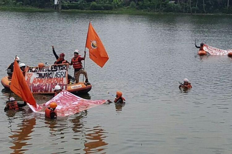 Aktivis lingkungan Ganespa ceburkan diri ke Situ Sasak Tinggi, Pamulang, Tangsel memprotes pembangunan Jalan Tol Cinere-Serpong yang menggusur sempadan situ, Kamis (1/3/2018).
