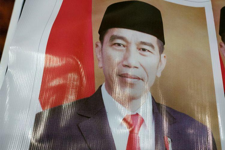Sejumlah pekerja di ruang Badan Anggaran (Banggar)  DPR Aceh sedang menggunting foto Presiden dan Wakil Presiden Joko Widodo-Maruf Amin dari spanduk untuk pajangan di setiap ruang di gedung DPR Aceh, Kamis (24/10/2019).