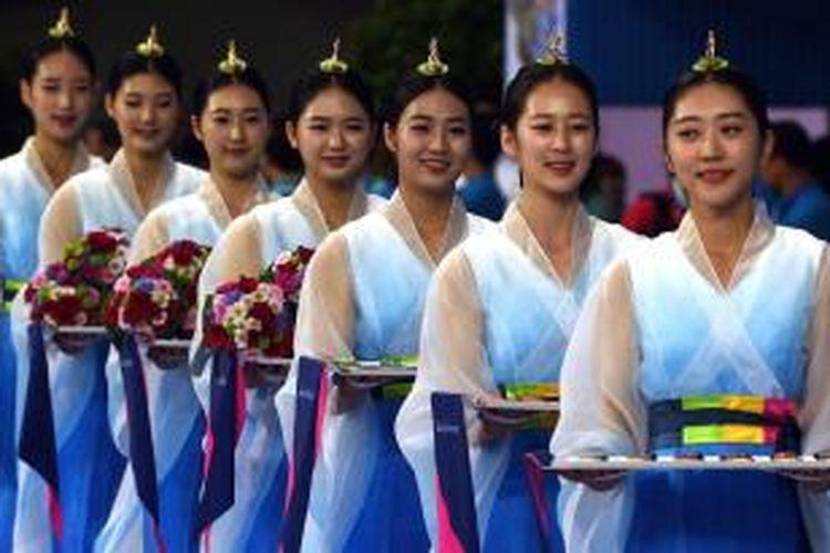 Gadis-gadis pembawa medali memasuki Namdong Gymnasium, pada upacara pemberian medali untuk cabang senam Asian Games 2014 di Incheon, Korea Selatan, Senin (22/9/2014).