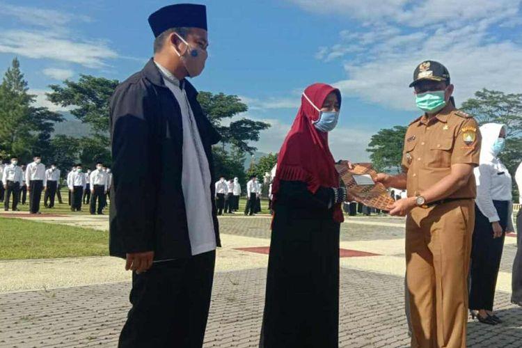Bupati Sumedang Dony Ahmad Munir menyerahkan penghargaan dan santunan kepada lima warga yang merelakan rumahnya dibongkar di lokasi longsor Cimanggung, Sumedang, 9 Januari 2021, lalu. AAM AMINULLAH