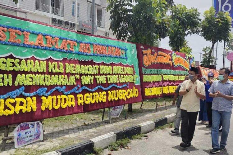 Ketua DPC Partai Demokrat Pekanbaru Agung Nugroho dan pengurus saat melihat karangan bungan ucapan selamat atas ditolaknya KLB kubu Moeldoko, yang dipajang di kawasan kantor DPC Demokrat Pekanbaru di Jalan Arifin Achmad, Kota Pekanbaru, Riau, Kamis (1/4/2021).