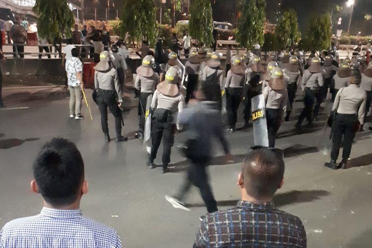 Polisi mengejar satu orang pemuda yang diduga menyebabkan kerusuhan saat demo mahasiswa dan pelajar di Jalan Gatot Subroto, Jakarta Selatan tepatnya di depan gedung Polda Metro Jaya, Jakarta Selatan, Senin (30/9/2019)