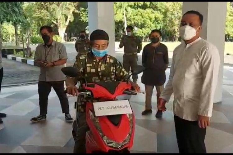 Safaruddin (64) sedang menerima hadiah sepeda motor dari Plt Gubernur, Sulawesi Selatan usai dirinya viral atas perjuangannya mengayuh sepeda sejaub 15 kilo meter dan harus berdiri kebingungan selama 6 jam lantaran tak tahu cara mendaftar daring sebagai peserta vaksimasi covid-19. Jumat, (31/7/2021).