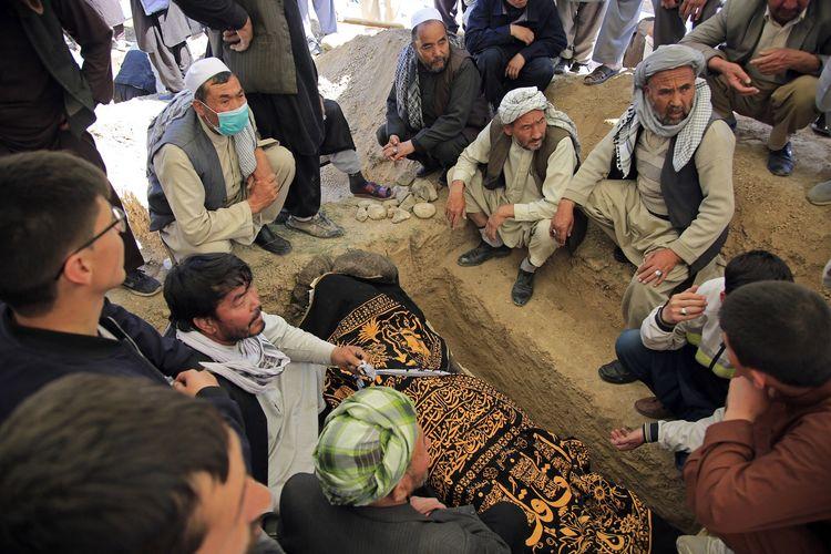Warga menguburkan jenazah korban ledakan bom yang terjadi Distrik Dasht-i-Barchi, Kabul, Afghanistan, pada 9 Mei 2021. Pemerintah menyatakan 68 orang tewas dalam serangan mengerikan yang tidak diketahui siapa dalangnya. Otoritas menyalahkan Taliban sebagai dalang serangan yang menimpa anak sekolah tersebut.