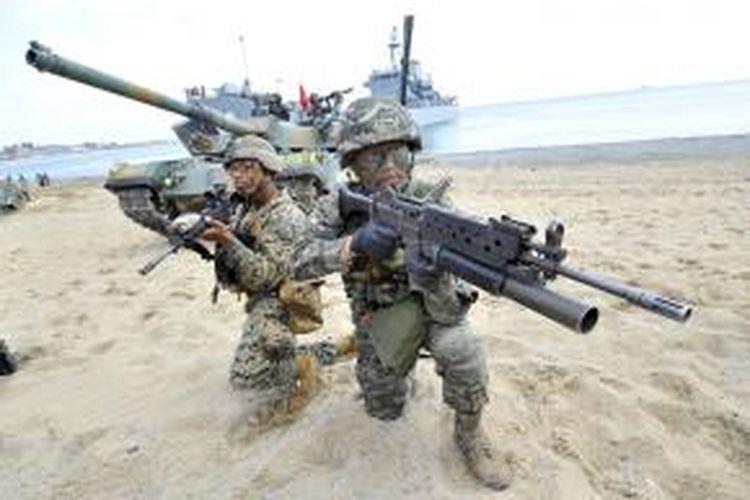 Dalam foto yang diambil pada 26 April 2013 menampilkan seorang prajurit marinir Kores Selatan (kanan) dan rekannya asal Amerika Serikat berlatih di pantai Pohang, 270 kilometer di sebelah tenggara Seoul.