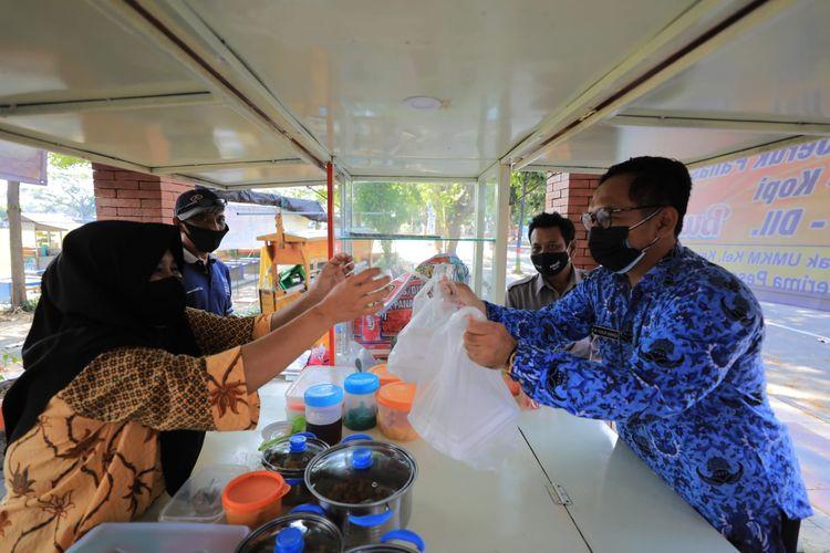 Seorang aparatur sipil negara (ASN) Pemkot Madiun belanja makanan di salah satu pedagang kaki lima. Walikota Madiun, Maidi mewajibkan ASN Pemkot Madiun belanjan kebutuhan harian ke UMKM  atau toko terdekat selama PPKM Darurat.