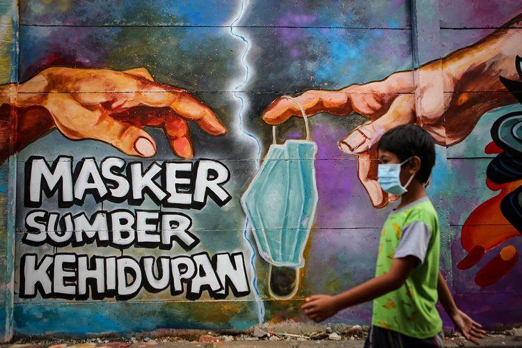 Seorang bocah melintas di depan mural tentang penggunaan masker di Kota Tangerang, Banten, Minggu (21/12/2020). Mural tersebut dibuat sebagai edukasi kepada masyarakat untuk selalu menggunakan masker guna mencegah penyebaran COVID-19. ANTARA FOTO/Fauzan/aww.