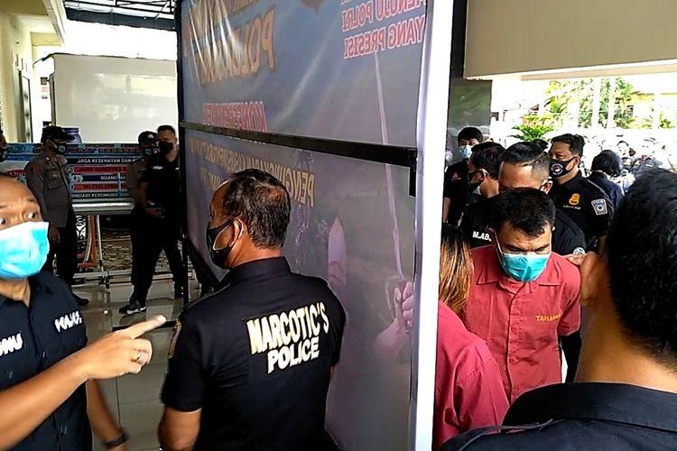 Man Batak (kanan) sedang berbicara dengan seorang tersangka lainnya usai konferensi pers di Mapolda Sumut tentang pengungkapan kasus sabu-sabu seberat 29,93 kg selama bulan Januari 2021. Man Batak merupakan bandar sabu-sabu terbesar di Labuhanbatu yang memiliki belasan sertifikat tanah seluas 13 hektare, air softgun, 5 mobil mewah, 4 rumah dan lainnya. Dia dijerat dengan UU tentang Narkotika dan UU TPPU.