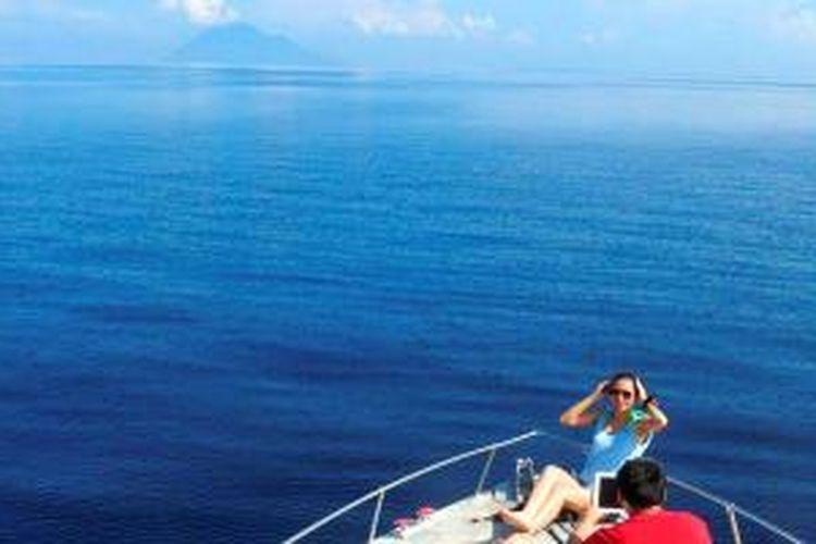 Bunaken, Sulawesi Utara, menjadi salah satu daya tarik bagi wisatawan  untuk datang ke  Manado. Di kapal yang membawa ke lokasi selam dan snorkeling, penumpang  berfoto dengan latar belakang Gunung Manado Tua dan Pulau Bunaken.