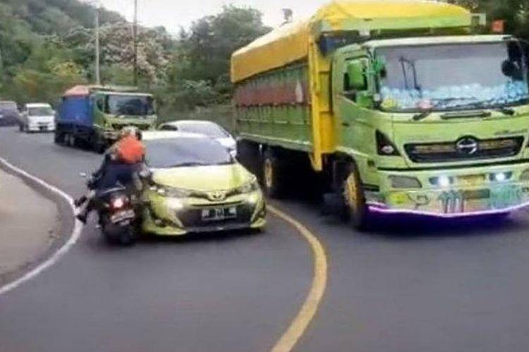 Tangkapan layar video yang menampilkan mobil Toyota Yaris menabrak pengendara sepeda motor ketika sedang menyalip di tikungan.