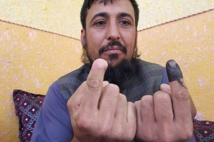 Pria Afghanistan, Safiullah Safi menunjukkan dua jari telunjuknya setelah menggunakan hak suaranya dalam pemilihan presiden 2019.
