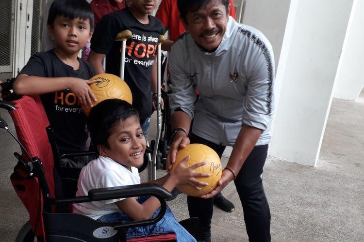 Pelatih tim nasional U-23 Indonesia, Indra Sjafri memberikan cenderamata pada salah seorang anak penderita kanker dalam kunjungan anak-anak penderita kanker ke lokasi latihan timnas U-23 di Stadion Madya, Kompleks Gelora Bung Karno, Jakarta, Rabu (13/3/2019) pagi.