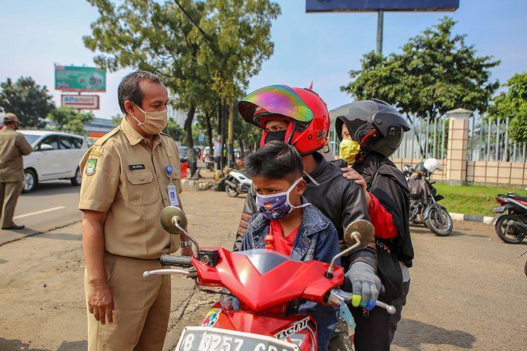 Petugas memeriksa pengendara saat penerapan Pembatasan Sosial Berskala Besar (PSBB) di jalan M.H Thamrin, Cikokol, Kota Tangerang, Banten, Sabtu (18/4/2020). Pemerintah telah resmi menerapkan PSBB di wilayah Tangerang Raya per hari ini dalam rangka percepatan penanganan COVID-19.
