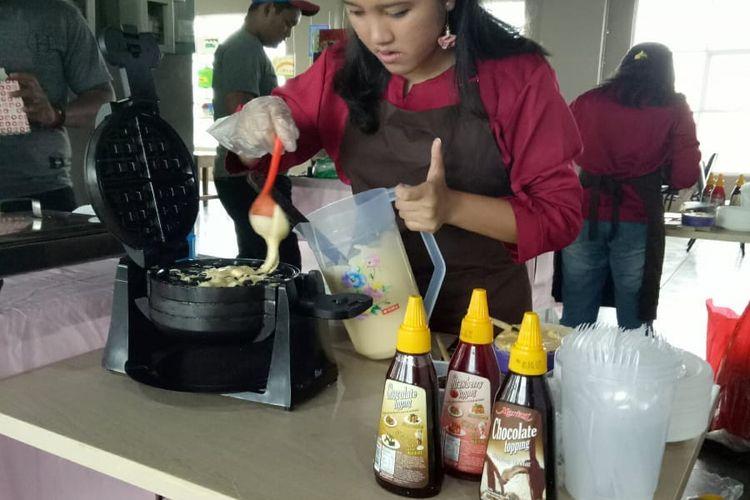 Purnama Sari Tampubolon mengolah masakannya.