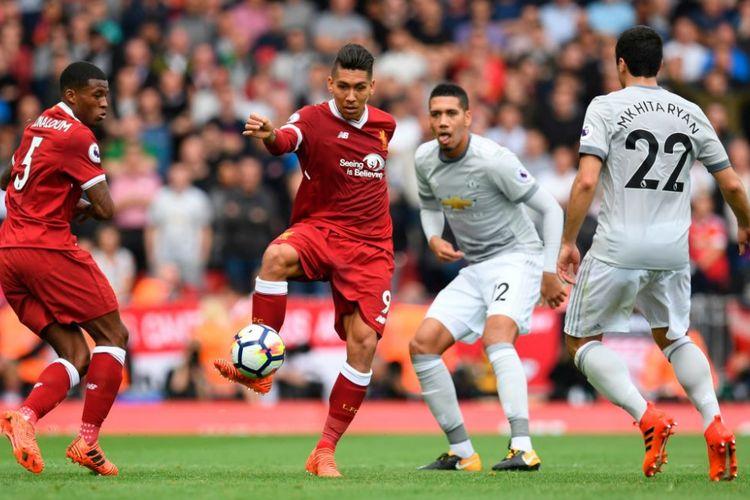 Disaksikan Georgionio Wijnaldum, Roberto Firmino mencoba melewat penjagaan Henrikh Mkhitaryan dan Chris Smalling saat Liverpool menjamu Manchester United di Anfield, Sabtu (14/10/2017).