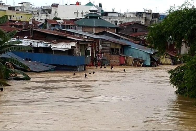 Sejumlah anak-anak muda berenang saat Sungai Deli meluap sejak Jumat (4/12/2020) dini hari. Ribuan rumah terendam banjir.