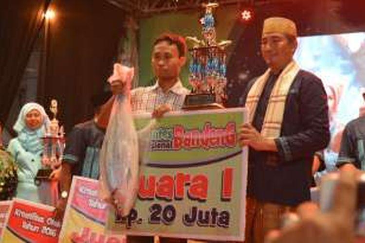Pemenang kontes bandeng Arif Rahman Hakim (kiri), saat foto bersama Kapolres Gresik AKBP Adex Yudiswan.