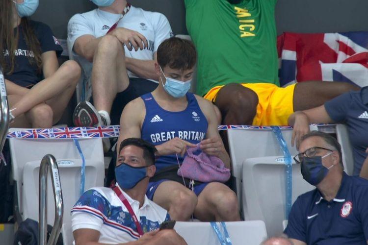 Atlet Loncat Indah asal Great Britain, Tom Daley, tertangkap kamera sedang merajut dari bangku penonton.
