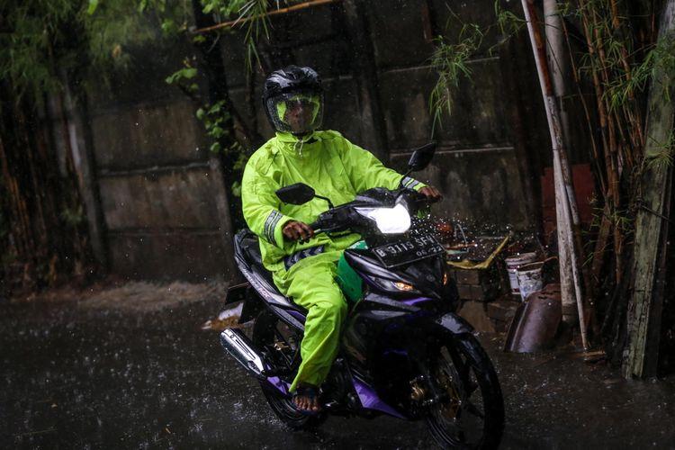 Pengendara sepeda motor melintas dibawah guyuran hujan lebat di jalan Karet Sawah, Jakarta Selatan, Senin (9/10/2017). Curah hujan yang tinggi menyebabkan sejumlah ruas jalan di Ibu Kota tergenang.