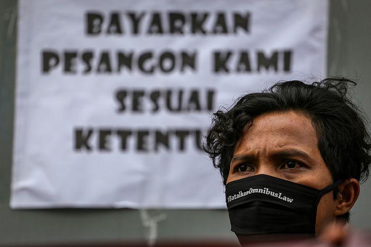 Seorang buruh mengikuti aksi unjuk rasa di depan pabrik tempat mereka bekerja di Benda, Kota Tangerang, Banten, Jumat (1/5/2020). Dalam aksi untuk memperingati Hari Buruh Internasional itu, massa menolak RUU Omnibus Law serta meminta pemerintah dan pengusaha untuk menjamin kelangsungan hidup buruh.