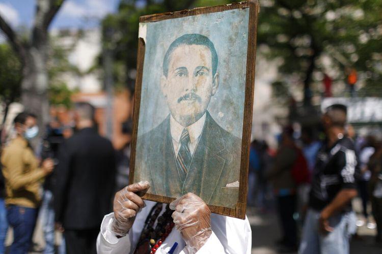 Umat memegang lukisan Venezuela Dr Jose Gregorio Hernandez, yang dibeatifikasi dan dikenal sebagai dokter orang miskin, oleh gereja Katolik, di Caracas, Venezuela, Jumat (30/4/2021).