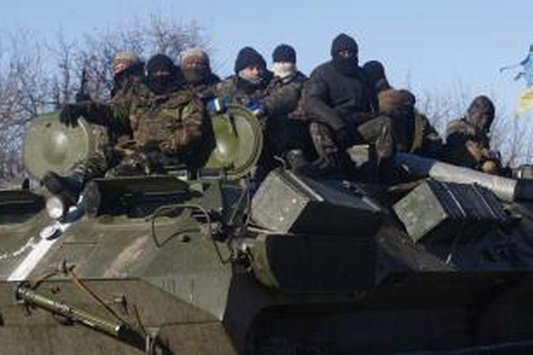 Sekelompok tentara Ukraina menumpang sebuah kendaraan lapis baja saat mereka ditarik mundur dari kota Debaltseve, Rabu (18/2/2015).