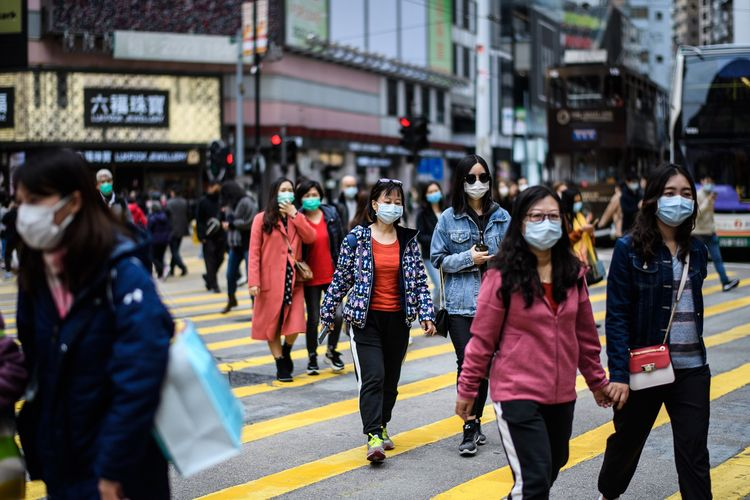 Pengguna jalan mengenakan masker melintas di jalanan Hong Kong di tengah masa liburan Tahun Baru Imlek pada 27 Januari 2020. Saat ini, China tengah dihantam virus corona yang sudah membunuh lebih dari 100 orang.