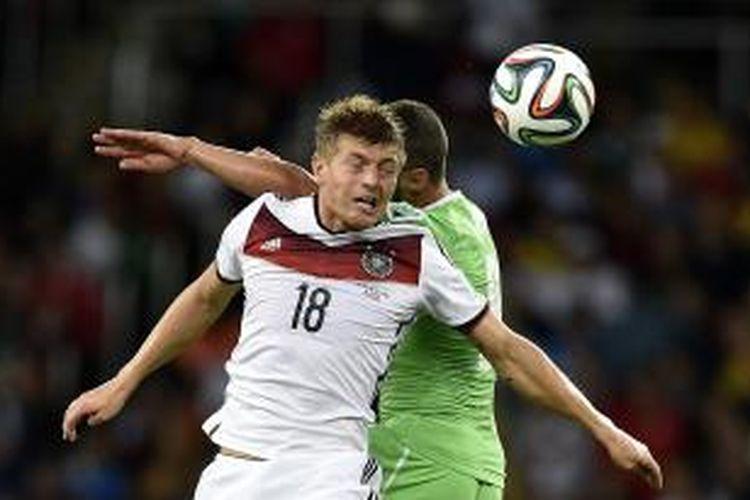 Gelandang Jerman, Toni Kroos, berebut bola dengan gelandang Aljazair Medhi Lacen, pada pertandingan 16 besar Piala Dunia, di Estadio Beira-Rio, Porto Alegre, 30 Juni 2014.