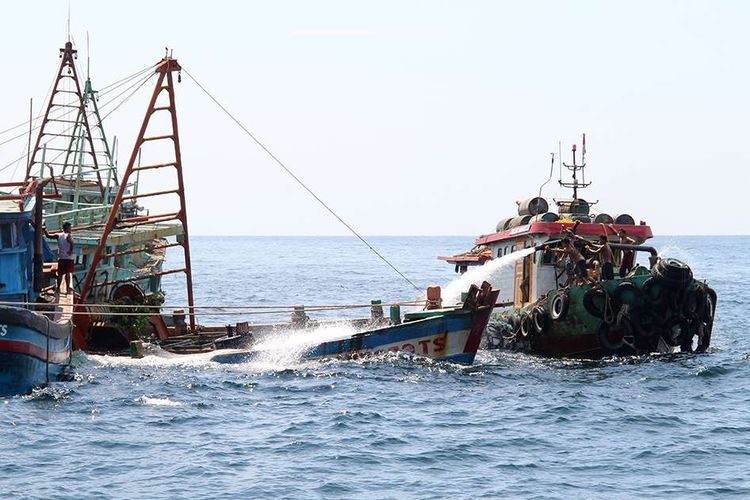 Sejumlah anak buah kapal bantu menyemprotkan air menggunakan mesin pompa ke dalam kapal nelayan Vietnam saat penenggelaman di Pulau Datuk, Kabupaten Mempawah, Kalimantan Barat, Sabtu (4/5/2019). Kementerian Kelautan dan Perikanan menenggelamkan 13 dari 51 kapal nelayan asing asal Vietnam yang ditangkap karena mencuri ikan di Perairan Indonesia.