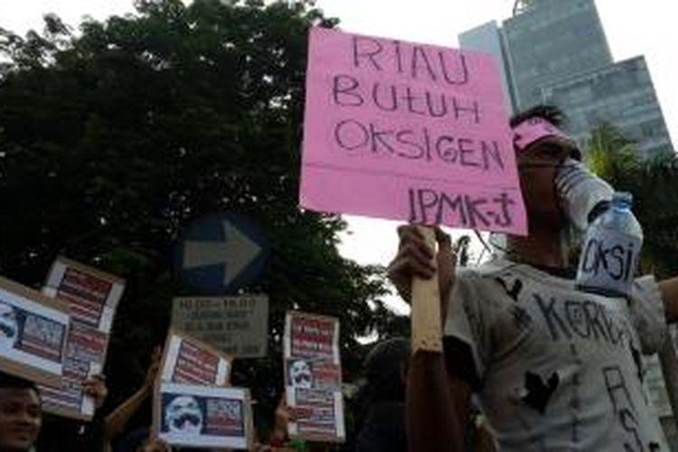 Aksi dari jurnalis lintas media menggelar #JurnalisPeduliAsap di Bundaran Hotel Indonesia, Jakarta, Minggu (11/10/2015).