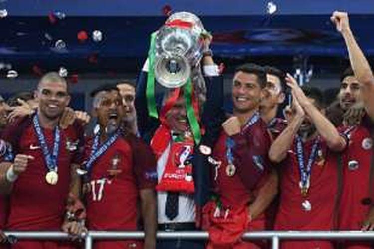 Fernando Santos mengangkat trofi Henri Delaunay seusai mengantarkan Portugal menjuarai Piala Eropa 2016, Minggu (10/7/2016).