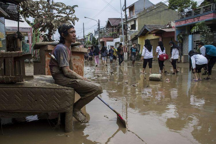 Sejumlah warga beristirahat usai membersihkan ruko miliknya yang sempat terendam banjir di kawasan Pondok Gede Permai, Jati Asih, Bekasi, Jawa Barat, Kamis(2/1/2020). Banjir di kawasan tersebut, merupakan banjir terparah di wilayah Bekasi.