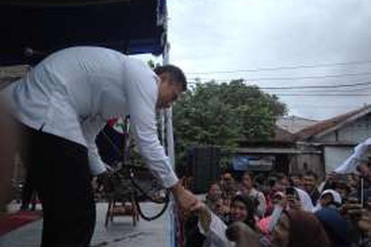 Calon gubernur DKI Jakarta, Agus Harimurti Yudhoyono saat diberikan hadiah oleh warga Poncol, Cilandak, Jakarta Selatan, Minggu (4/12/2016).