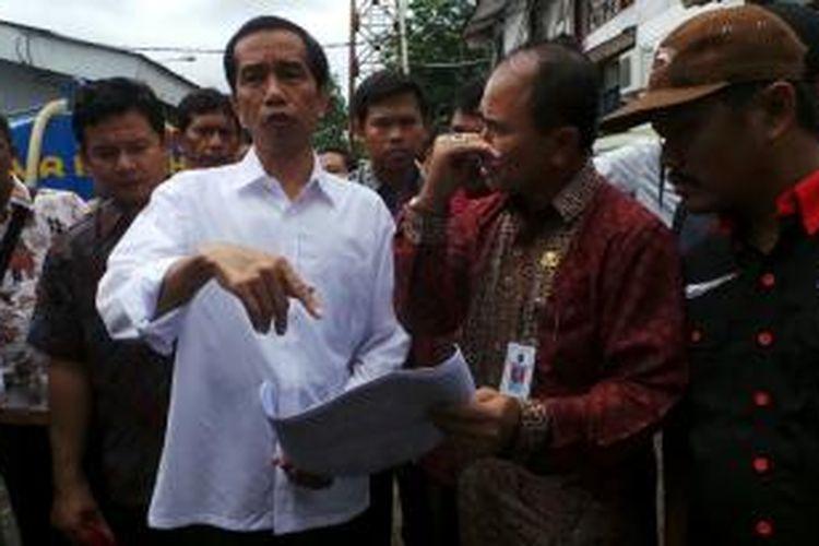 Gubernur DKI Jakarta Joko Widodo mengunjungi korban banjir di Rawa Buaya, Cengkareng, Jakarta Barat, Kamis (16/1/2014). Di sana ia menyerahkan bantuan berupa beras dan alat-alat tulis.
