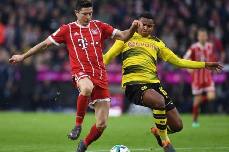 Robert Lewandowski mendapat pengawalan dari Manuel Akanji ketika Bayern Muenchen menjamu Borussia Dortmund di Stadion Allianz Arena pada laga Bundesliga, Sabtu (31/3/2018).