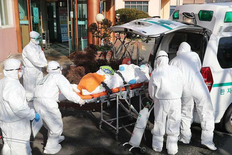 Para pekerja medis dilengkapi pakaian pelindung memindahkan seorang pasien diduga terinfeksi virus corona (tengah) ke rumah sakit lain dari Rumah Sakit Daenam, di daerah Cheongdo, Korea Selatan, Jumat (21/2/2020). Penyebaran virus corona hingga hari ini, Senin (24/2/2020), semakin menunjukkan peningkatan di sejumlah negara, seperti Italia, Iran, dan Korea Selatan.
