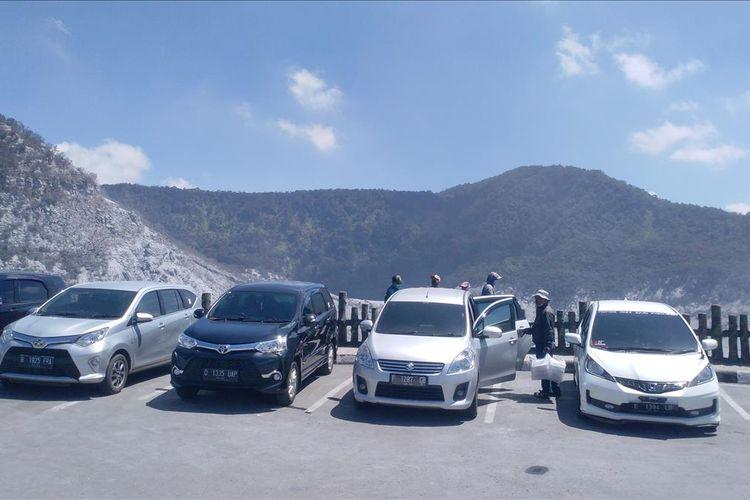 Mobil wisatawan yang diparkir membelakangi Kawah Ratu, pusat kunjungan wisata Gunung Tangkuban Parahu.