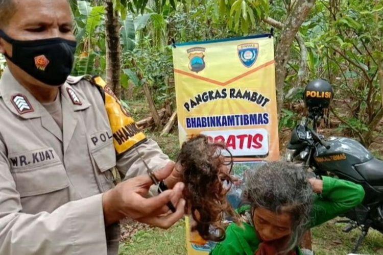 Bripka Warokhmat Kuat, Bhabinkamtibmas Polsek Poncowarno, Kebumen, Jawa Tengah, memotong rambut warganya yang tak terurus hingga menjadi gimbal.