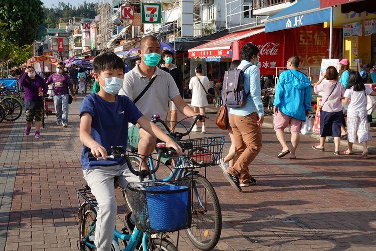 Warga Hong Kong terlihat memakai masker bepergian di pulau Cheung Chau saat libur Paskah, di tengah merebaknya virus corona. Foto diambil pada 12 April 2020.