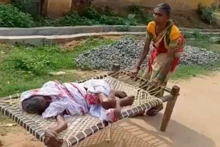 Gunja Dei, warga di Odisha, India, ketika membawa ibunya yang berusia 100 tahun, Labhe Baghel, lewat ranjang anyaman ke bank. Dia melakukannya setelah bank menolak pencairan uang dengan alasan ibunya harus hadir.