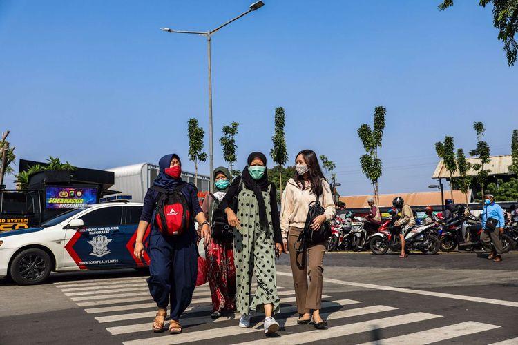 Pekerja menggunakan masker saat berjalan menuju perkantoran di Kawasan Tanah Abang, Jakarta Pusat, Senin (21/9/2020). PSBB kembali diterapkan mulai tanggal 14 September 2020, berbagai aktivitas kembali dibatasi yakni aktivitas perkantoran, usaha, transportasi, hingga fasilitas umum.