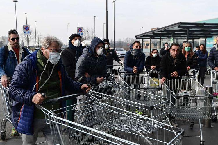 Warga menunggu diberikan akses sebelum bisa berbelanja di sebuah supermarket di kota kecil Italia, Casalpusterlengo, terkait pemeriksaan virus corona, Minggu (23/2/2020). Penyebaran virus corona hingga hari ini, Senin (24/2/2020), semakin menunjukkan peningkatan di sejumlah negara, seperti Italia, Iran, dan Korea Selatan.