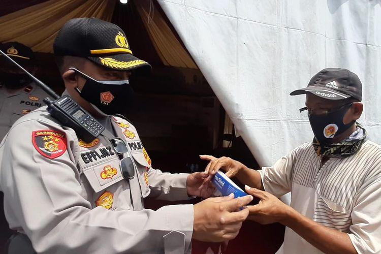 Kapolsek Pasar Minggu, Kompol Effi Zulkifli membagikan face shield kepada masyarakat di Pos Pengamanan Natal dan Tahun Baru 2021 di dekat PD Pasar Minggu di Jalan Raya Ragunan, Pasar Minggu, Jakarta Selatan pada Rabu (23/12/2020).