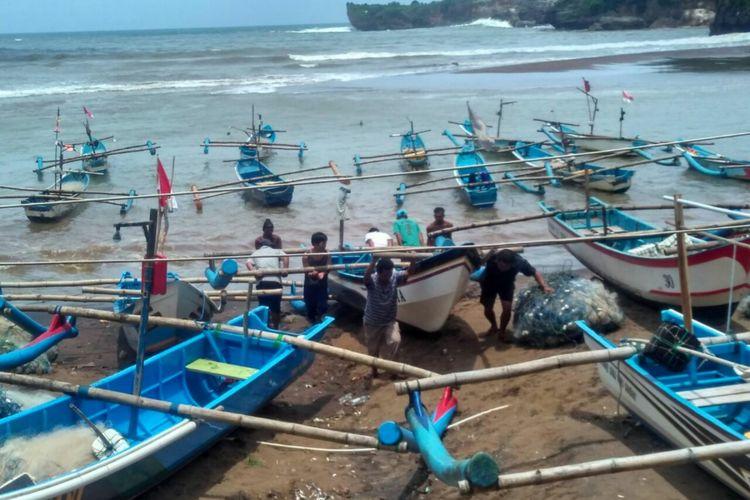 Nelayan Pantai Baron memindahkan kapal jukung ke tepian.