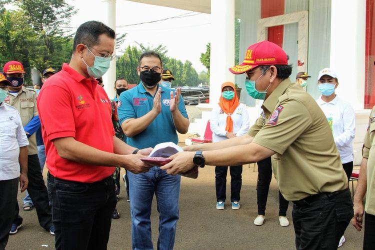 Menteri Sosial Juliari P. Batubara menyerahkan cinderamata kepada perwakilan Taruna Siaga Bencana (Tagana), di halaman Gedung Konvensi di Gedung Konvensi Kompleks Taman Makam Pahlawan Nasional Utama (TMPNU) Kalibata, Jakarta (19/04/2020).