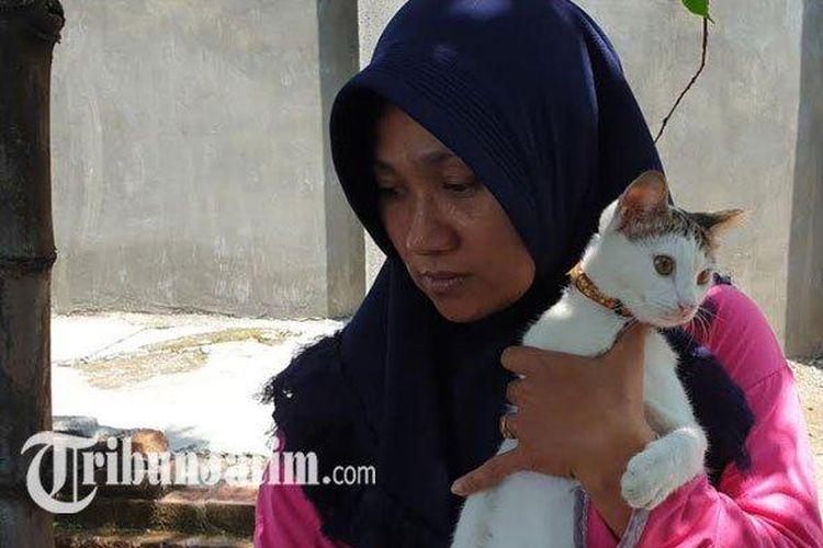 Widarti, pemilik rumah menggendong si putih kucing peliharaannya yang berhasil mengusir ular kobra agar tidak masuk ke dalam rumahnya.